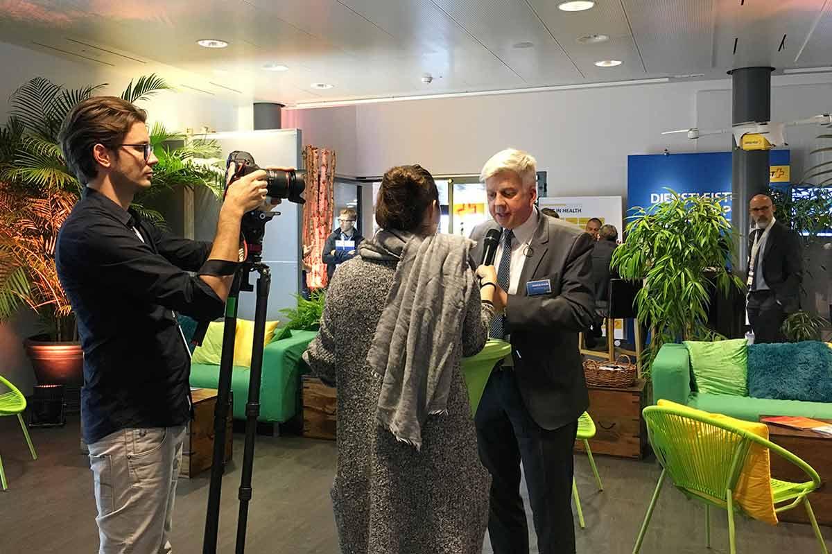 Mann wird von Frau interviewt, daneben der Kameramann