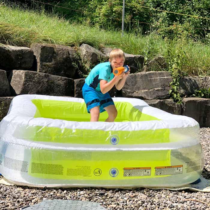 Junge mit Wasserpistole im Bassin