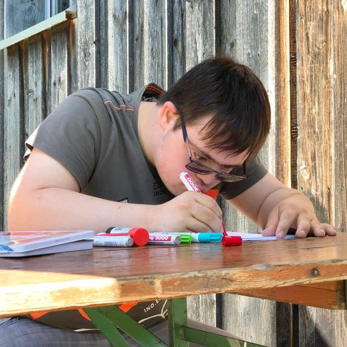 Junge mit Behinderung malt
