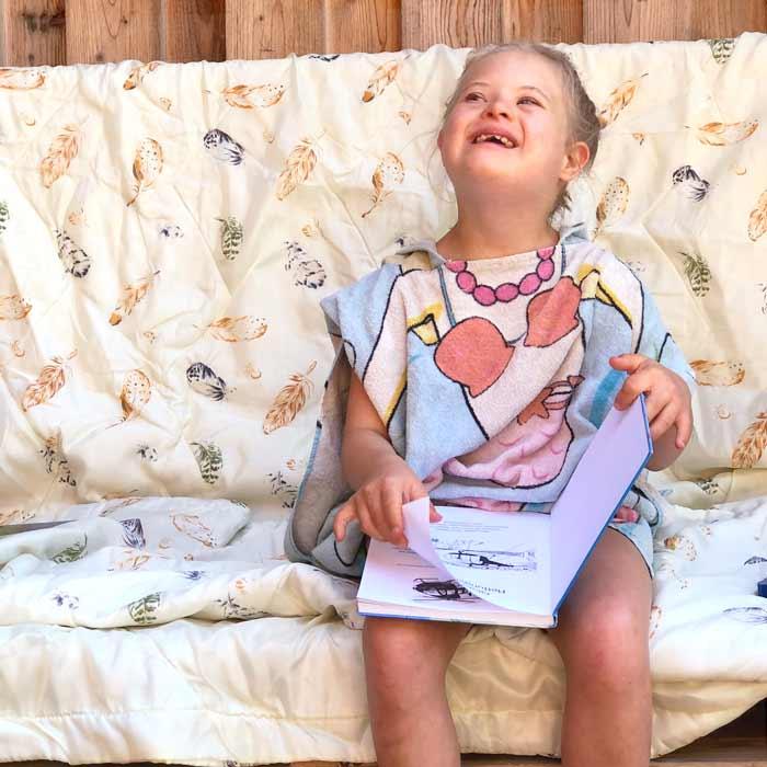 Mädchen mit Behinderung sitzt auf Sofa und liest ein Buch