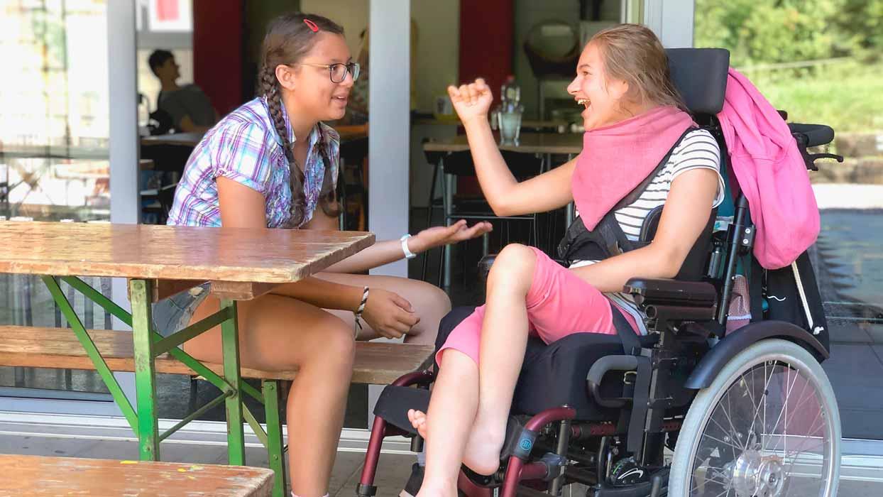 Zwei Mädchen sprechen und lachen miteinander